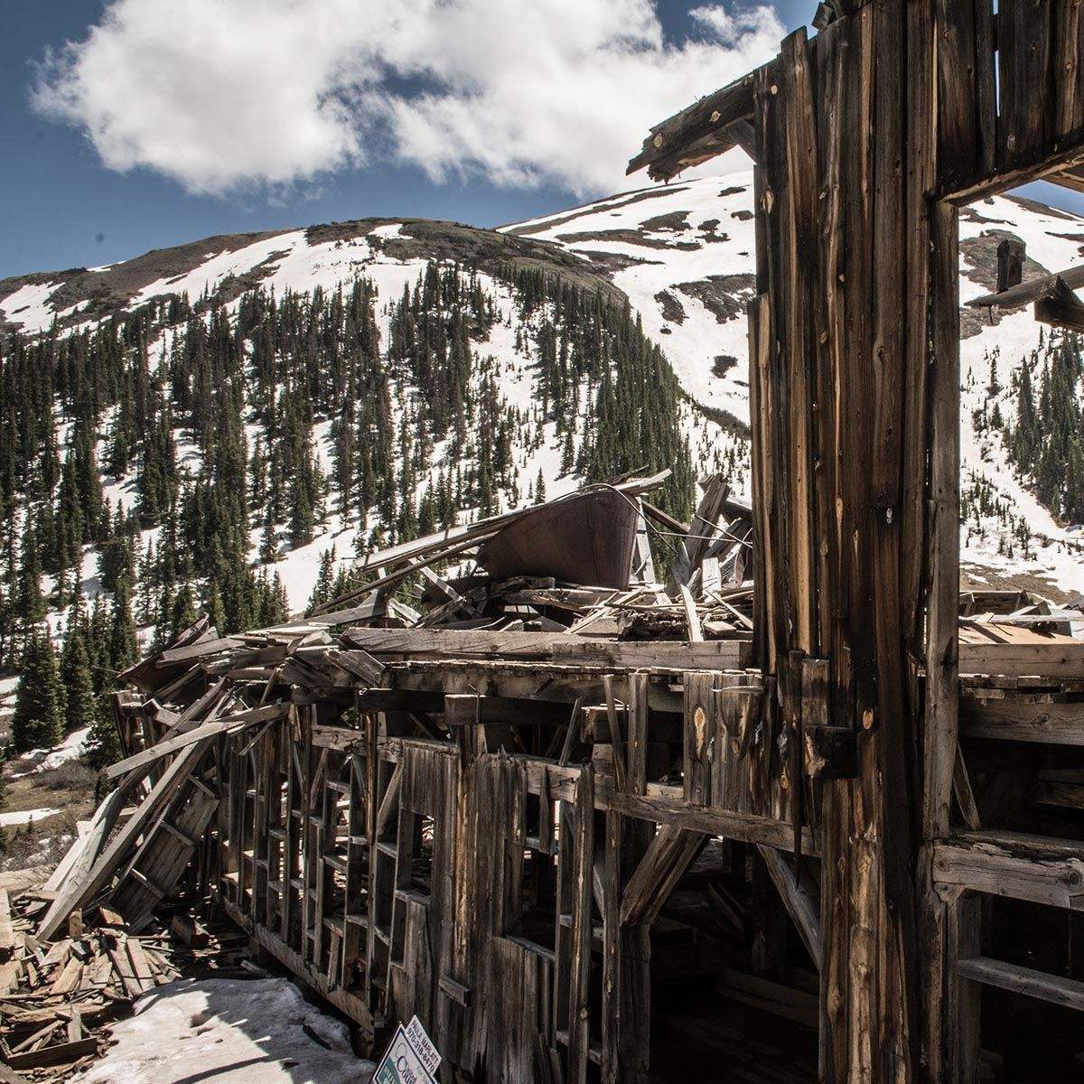 destroyed wooden house with snowy mountains in the background